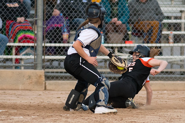 Farmington's Kaitlyn Hand slides under the tag of Mankato East catcher Maddie Glogowski in Friday's game played at Caswell Park. The Cougars defeated Cretin-Derham Hall in the opening game but lost to Farmington and will play for third place in the Mankato East Invitational today. Photo by Jackson Forderer