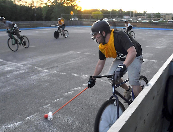 Andy Dowd brings the ball up the boards during a bike polo match Thursday at the Stoltzman Road rink.