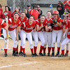 Mankato West's Callie Looft is welcomed home by her teammates after hitting a two-run home run to put West ahead of Mankato East in the sixth inning of their game Friday at Thomas Park.  Photo by Pat Christman