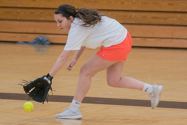 Lily Andrego of Mankato East backhands a ground ball hit to her during practice in the East gym on Thursday. Andrego is the only senior on the Cougars softball team this season. Photo by Jackson Forderer