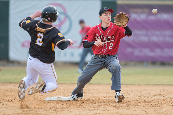 Mankato West's Benjamin Hopper (right) makes a force out at second base on Mankato East's Isaac Turner during Thursday's game played at Wolverton Field. The Cougars won their home opener 6-1 over the Scarlets. Photo by Jackson Forderer
