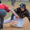 Mankato East's Walker Reyes (right) tries to avoid a tag from Mankato West's Kyle Liebl while sliding back to first base during Thursday's game. It was the first game of the season for both East and West, with East coming out on top 6-1. Photo by Jackson Forderer