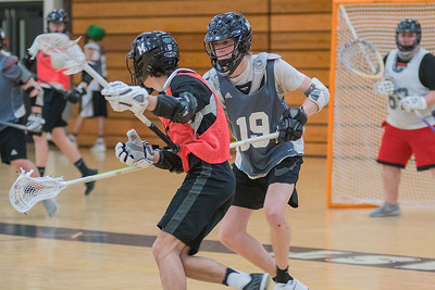 Josh Etter (19) defends a teammate during practice in the Mankato East gym on Tuesday. Etter is a returning senior defensemen for the Mankato boys lacrosse team. Photo by Jackson Forderer