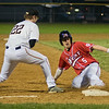 Mankato West's Ben Scott slides safely into third ahead of a tag by Jack Allan of Mankato East. Scott's triple scored two runs to help the Scarlets win 3-0 over the Cougars. Photo by Jackson Forderer