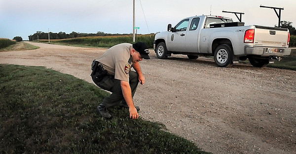 John Cross<br /> Minnesota Department of Natural Resources Conservation Officer Bob Geving checks dew conditions before beginning an annual roadside wildlife county last week.