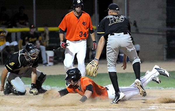 Willmar pitcher Michael Hahn can only watch as Mankato MoonDogs' Craig Massoni scores from third on a wild pitch as catcher JD Dorgan scrambles for the ball during the third inning of their playoff game Wednesday at Franklin Rogers Park. Massoni's teammate Chad Christensen looks on.