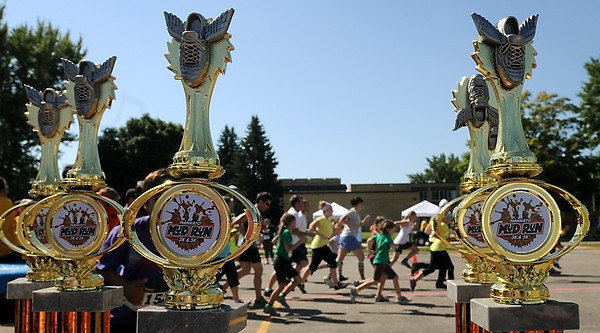 John Cross<br /> Runners setting out on the Mankato Mud Run's 3K family run are framed by trophies awarded to competitors in the timed 5K event.