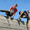 John Cross<br /> Muddied participants in the Mankato Mud Run throw themselves over an obstacle along the course.