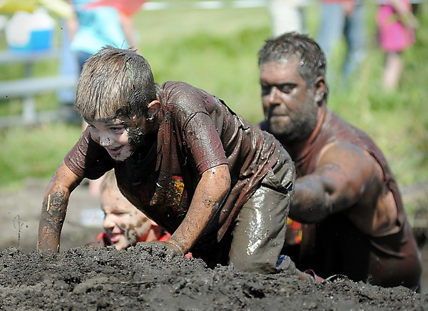 John Cross<br /> A young Mankato Mud Run participant gets a helping hand from behind as he struggles out of a mud pit.