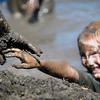John Cross<br /> A young competitor is offered a helping hand at a mud pit during the Mankato Mud Run.