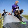 Runners negotiate an obstacle created by two cars during the Mankato Mud Run on Saturday at Good Counsel Hill.