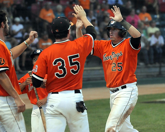 The MoonDogs' Brent Zimmerman is congratulated by teammates after scoring a run in the fifth inning of the Summer Collegiate World Series game Thursday at Franklin Rogers Park. Photo by Pat Christman