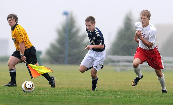 Chanhassen's Spencer Franks and Manakto West's Samuel Oudekerk charge after the ball during a rainy first half Saturday at Dakota Meadows Middle School.