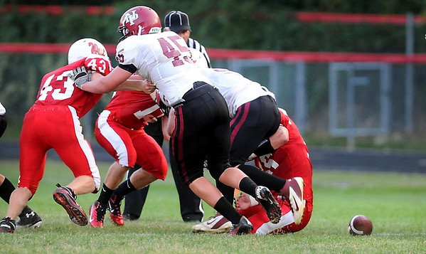 The ball lays on the ground near a pile of Mankato West and New Prague players after a fumble during the first half Thursday.
