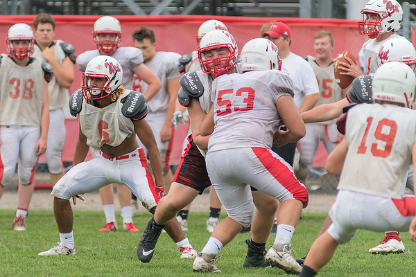 Garrett Shumski (center) blocks a teammate during an offensive drill at a Mankato West football practice. Photo by Jackson Forderer