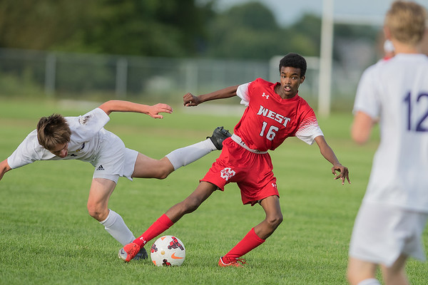 Amed Mohamed of Mankato West escapes Red Wing's Aidan Coyle's attempt to steal the ball during the first half of Tuesday's game. The Scarlets won the match 4-2. Photo by Jackson Forderer