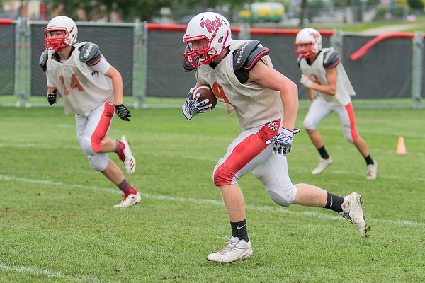Mankato West's Clay Herding (center) returns an interception during a defensive drill at practice. Herding and the Scarlets hope to return to state this year. Photo by Jackson Forderer