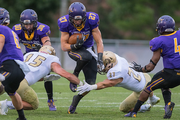 Minnesota State's Justin Arnold tries to squeeze between two Southwest Minnesota State University players Hunter Cushman (15) and Ben Specht (27) during a punt return. Arnold also had four catches for 75 yards in the 49-13 Mavericks win. Photo by Jackson Forderer