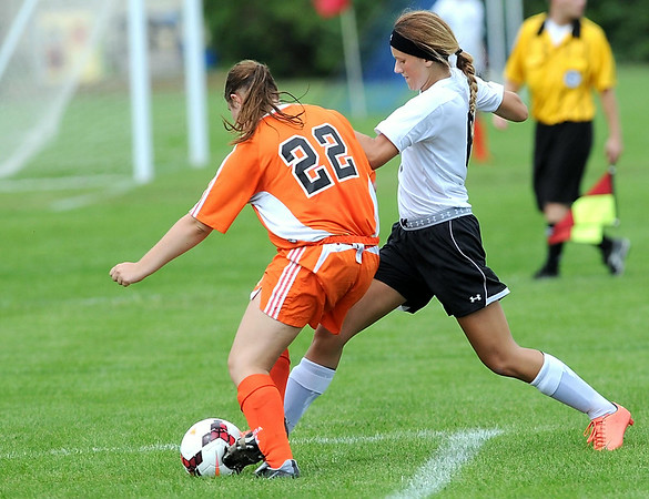 Manakto East's Taylor Kuechle kicks the ball past Winona's Kambia Bothun during the second half Saturday. Photo by Pat Christman
