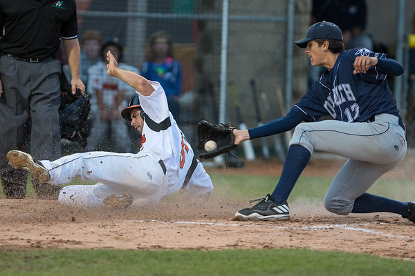 Daniel Amaral of the MoonDogs slides safely into home ahead of a tag from Duluth Huskies pitcher Nick Scheidler (17). Amaral stole home after a wild pitch was thrown by Scheidler. Photo by Jackson Forderer