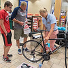 Megan Christopher (right) shows Pat Berry (middle) and his son Zach Berry, 15, where to put their number on their bike for the upcoming triathlon that will be held on Sunday in North Mankato. It will be both Pat and Zach's first time ever participating in a triathlon. Photo by Jackson Forderer