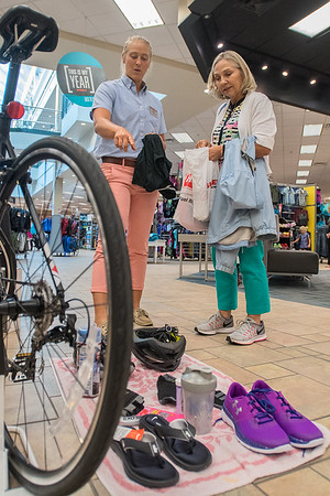Megan Christopher (left) shows Gale Wilking an example transition mat at Scheel's for Sunday's triathlon to be held in North Mankato. It will be Wilking's first ever triathlon. Photo by Jackson Forderer