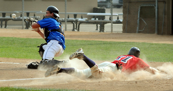 Austin's John Fein is safe at home as Mets catcher Mitch Kleist shags a wide through during second inning action at Franklin Rogers Park on Saturday. Photo by John Cross