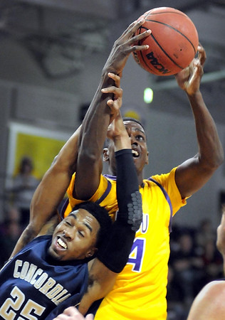 Minnesota State's Jarvis Williams reaches over Concordia University's Terez VanPelt for a rebound during the first half Saturday at Bresnan Arena.