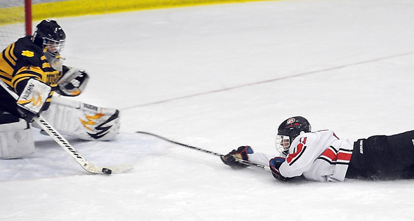 Pat Christman<br /> Mankato East/Loyola goalie 1 brushes the puck away from a sliding Dylan Leivermann of Mankato West during the first period Tuesday at All Seasons Arena.