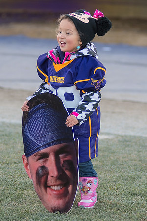 Trevor Nissen's niece, Mia Russ, 3, holds a fat head of him on the field after the game. Nissan is a junior tight end on the Maverick football team. Photo by Jackson Forderer