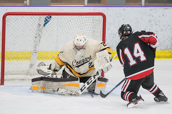 Mankato East goalie Jack Cusey stops a shot from Rochester John Marshall's Nick Hackman on a break away during Tuesday's Big Nine conference game held at All Seasons Arena. Photo by Jackson Forderer
