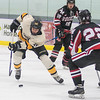 Mankato East's Sam Schulz skates into the offensive zone against Rochester John Marshall's Jason Coyle (22) during Tuesday's Big Nine conference game played at the All Season Arena. Schulz scored East's first goal of the game on a breakaway to help the Cougars to a 3-1 victory. Photo by Jackson Forderer