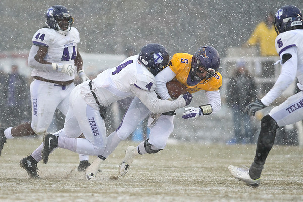 Minnesota State's Ryan Schlichte dives forward while being tackled by Tarleton State's Ronnell Wilson in Saturday's playoff game. Photo by Jackson Forderer