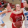 Mankato West's Lani Schoper is fouled by Owatonna's Emma Dahnert on her way to the basket in the second half of Friday's game. The Scarlets won their home opener 62-31. Photo by Jackson Forderer