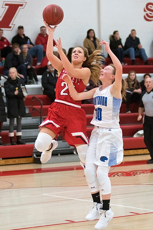 Emily Fitterer of Mankato West goes in for a layup over Owatonna's Arianna Shornock in the second half of Friday's game played at West. The Scarlets built their lead in the second half to win 62-31. Photo by Jackson Forderer