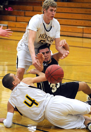 Mankato East's Brandon Adema (33) scrambles for the ball as Hutchinson's Matt Kieser (50) and Alex Aalfs surround him during the first half Saturday at the East gym.