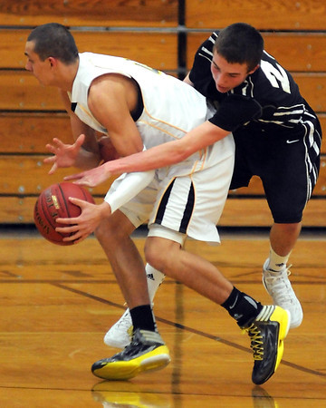 Mankato East's Nic Seiler leaps around Hutchinson's Alex Aalfs as he goes for the steal during the first half Saturday at the East gym.