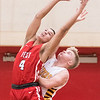 Mankato West forward Dondre Span (4) grabs a rebound over Northfield's Carter Hodapp early in the first half of their game played at Mankato West High School. Photo by Casey Ek