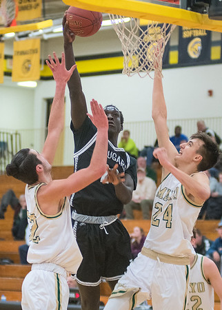 Uhana Ochan of Mankato East puts up a shot over Rochester Mayo's Adam Leary (left) and Kyle Kriener during Thursday's Big Nine conference game. Photo by Jackson Forderer