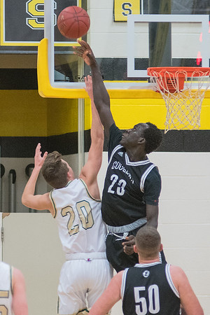 Ghana Ochan of Mankato East rejects a shot by Rochester Mayo's Stephen Douglas (20) in the second half of Thursday's game played at East. East rallied from behind to defeat Mayo 78-71. Photo by Jackson Forderer