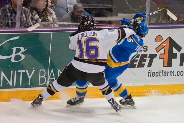 Jordan Nelson collides with a Alaska Nanooks player while heading into the boards in the first period. Photo by Jackson Forderer