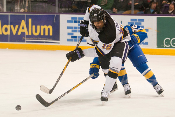 C.J. Franklin (15) of Minnesota State tries to elude an Alaskan Nanooks defender in the offensive zone in the second period. Photo by Jackson Forderer