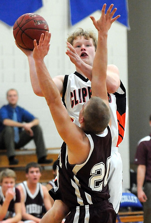 Pat Christman<br /> Cleveland's Spencer Davies shoots around the outstretched arms of New Ulm Cathedral's Brandon Beranek during the first half Friday in Nicollet.