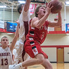 St. Clair's Brandon Schultz (3) drives the lane and puts up a shot underneath the outstretched arm of Fairmont's Derek Missling during the first round of the Kwik Trip Holiday Tournament played at Bethany Lutheran College. Photo by Jackson Forderer