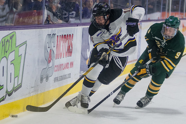 Minnesota State's Zeb Knutson gets control of the puck in the corner while being chased down by Northern Michigan's Troy Loggins (9) during the second period of Friday's game. Photo by Jackson Forderer