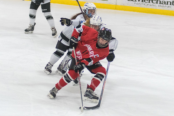 Mankato West's Lindsey Hays tries to get around the defense of Minnesota River Valley's Ella Boomgaarden in the second period during Saturday's game at the Lady Bulldog Hockey Tournament played in Le Sueur. The Scarlets won the game 4-0. Photo by Jackson Forderer