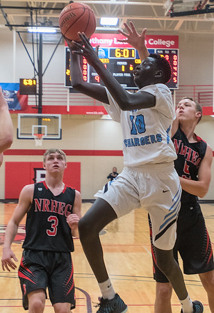 Minnesota Valley Lutheran's Dunwa Omot puts up a floater past New Richland-Hartland-Ellendale-Geneva's Blake Ihrke (right) in the first half of the Kwik Trip Holiday Tournament semifinal game played at Bethany Lutheran. Photo by Jackson Forderer