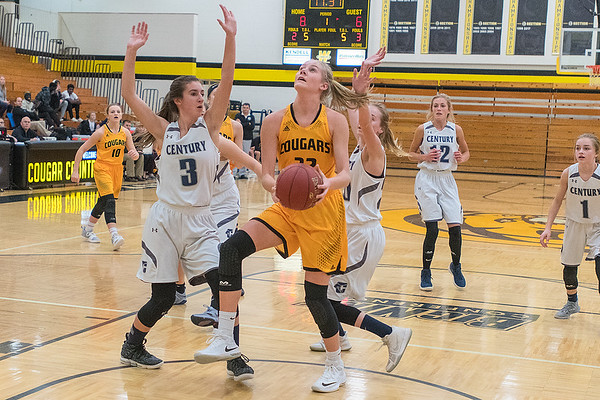 Mankato East's Lexi Karge (center) goes up for a shot while being defended by Rochester Century's Sydney Sukalski early in the first half of Friday's Big Nine game. The Cougars won the game 63-36. Photo by Jackson Forderer
