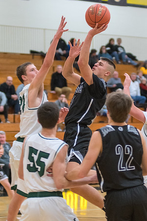 Mankato East's Jax Madson puts up a shot over Faribault's Nick Ehlers in the first half of Friday's game. Madson scored 22 for the Cougars who won the game 74-33. Photo by Jackson Forderer