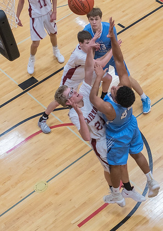 Minnesota Valley Lutheran's Izayah Harrison puts up a shot over Fairmont's Joey Flohrs. The Chargers lost the championship game 56-53 to the Cardinals. Photo by Jackson Forderer